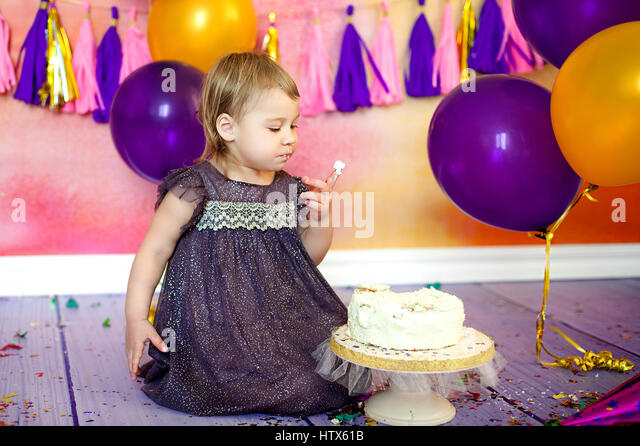 Two year old baby eating cake. Holiday birthday. Decor garlands and balloons - Stock Image