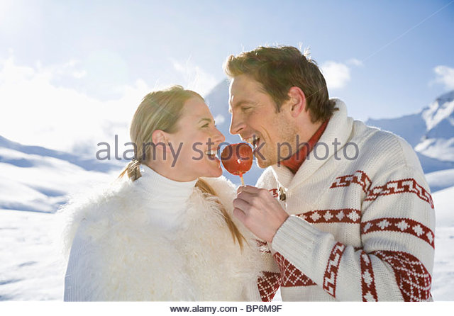 Young couple eating candy apple on winter day - Stock Image