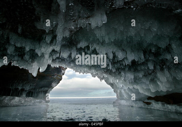 Ice hanging from arch in sea cave carved in soft sandstone cliffs, frozen lake, Squaw Bay, Lake Superior, Apostle - Stock Image