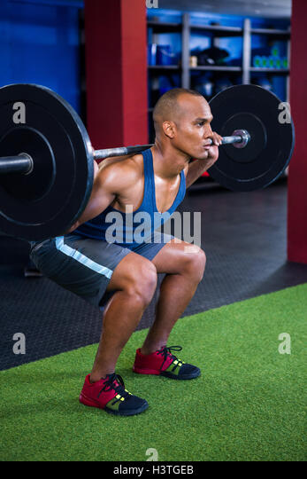 Determined young man weightlifting - Stock Image