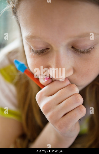 Girl concentrating on her homework - Stock Image