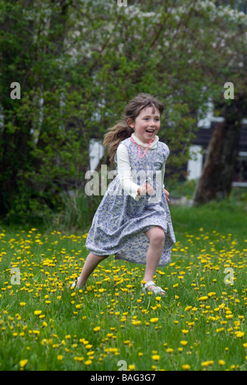 Young girl running through flowers Pemperton British Columbia Canada - Stock Image