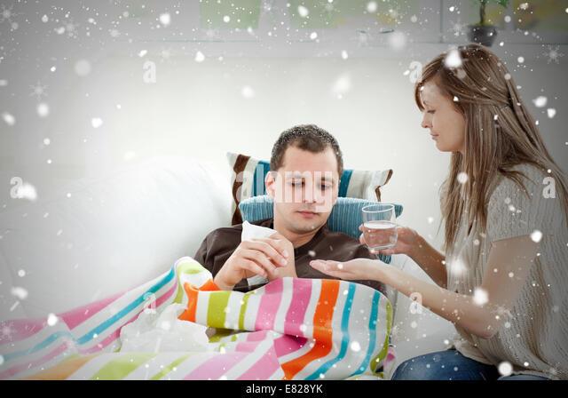 Caring girlfriend giving his sick boyfriend pill - Stock Image