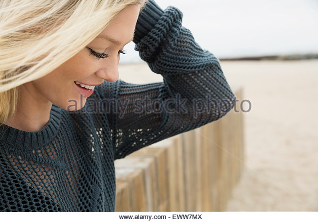 Blonde woman looking down at beach - Stock Image