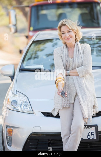 Portrait of smiling woman waiting for roadside assistance - Stock Image