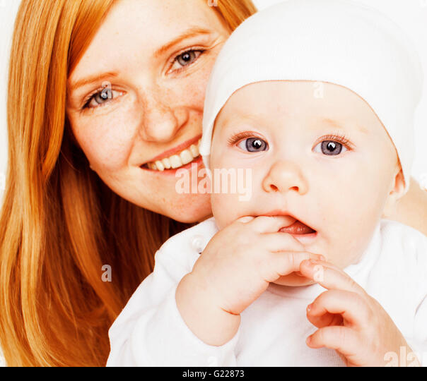 young beauty mother with baby, red head happy family isolated close up - Stock Image