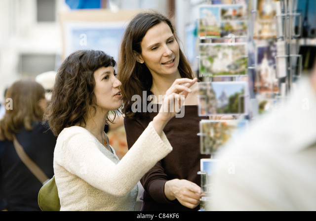 Female tourists looking at postcards - Stock Image