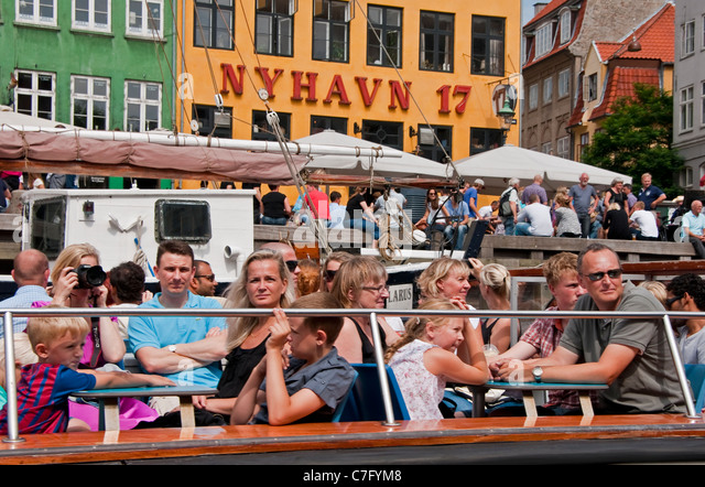Tourists on Copenhagen canal cruise tour boat in Nyhavn - Stock Image