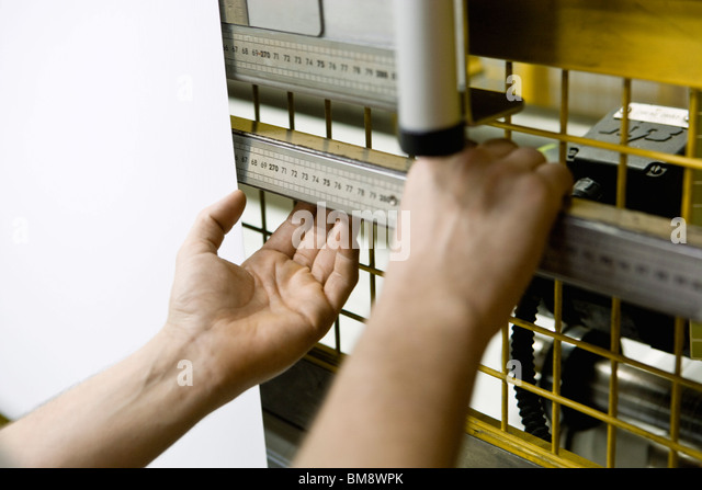 Fabric coating plant, machinist working on production line - Stock Image