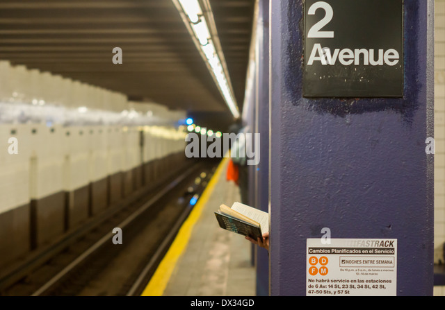 A woman reads a hardcover book on the Second Avenue platform in the New York subway - Stock Image