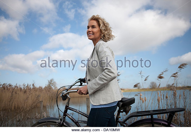 A mature woman standing beside a lake with a bicycle - Stock Image