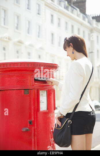 Young Woman Mailing Letter in Red Postbox, London, England, UK - Stock Image