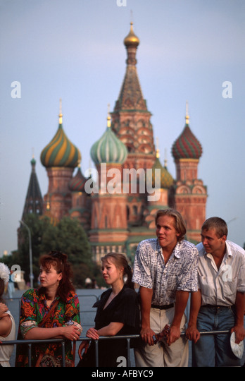 Russia former Soviet Union Moscow Red Square St. Basil's Cathedral by Ivan the Terrible young adults watch videotaping - Stock Image