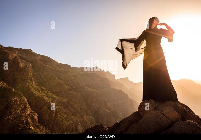 Lone woman in abaya in Al Hajar Mountains of Oman at sunset - Stock Image