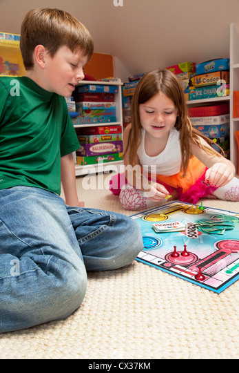 A brother and sister are playing a board game together. - Stock Image