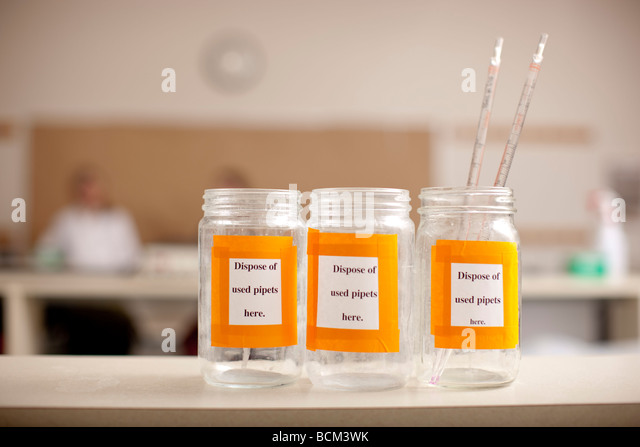 Glass bottles in classroom lab for disposal of Pipets - Stock Image