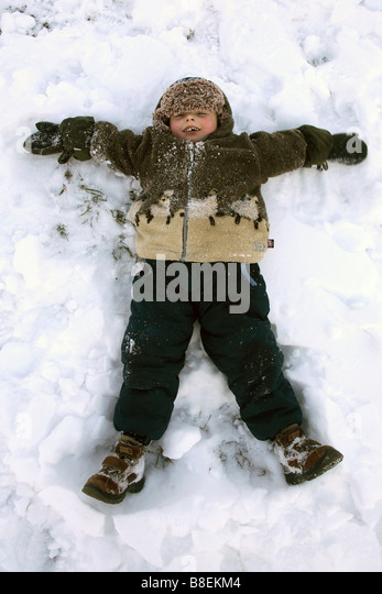 Kid making a snow angel - Stock Image