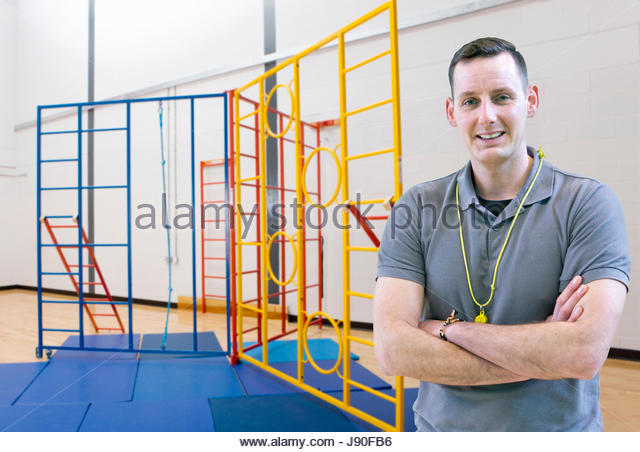 Portrait Of Male Sports Coach Standing In Gymnasium - Stock-Bilder