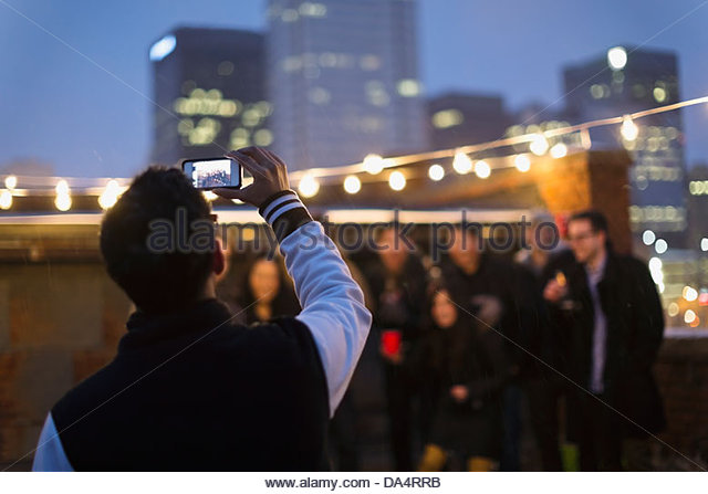 Entrepreneur taking photograph of colleagues on rooftop - Stock Image
