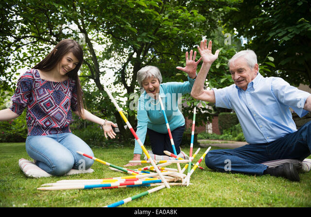 Grandparents and granddaughter playing giant pick up sticks - Stock Image