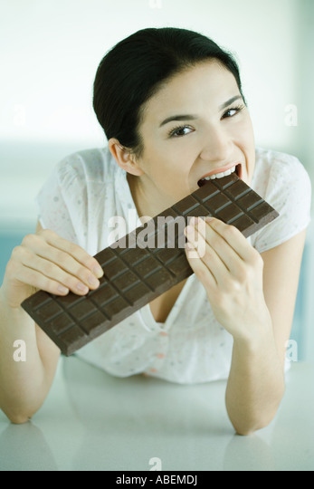 Woman biting into large bar of chocolate - Stock Image
