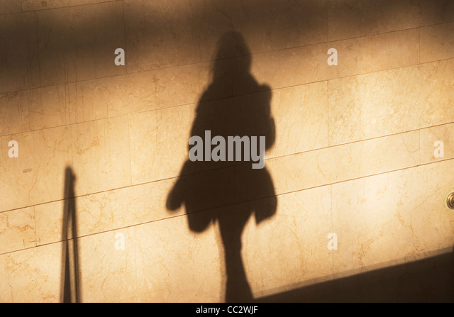 USA, New York City, Shadow of female pedestrian on sunlit wall - Stock Image