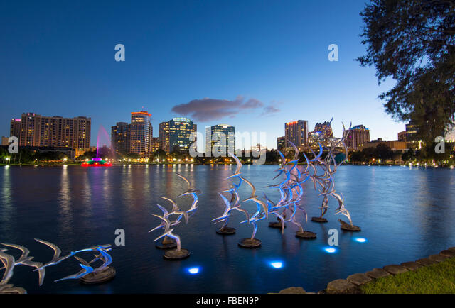 Orlando Florida Lake Eola Take Flight Douse Blumberg skyline twilight night colored lights on birds statue night - Stock Image