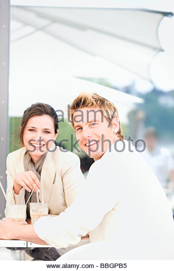 Young couple drinking milkshakes at outdoor café, Stuttgart, Baden-Wurttemberg, Germany - Stock Image