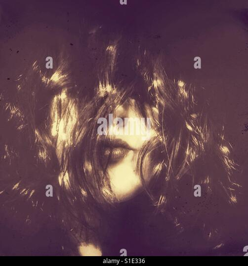 Woman's face with hair all around her face and shining light in retro style - Stock-Bilder