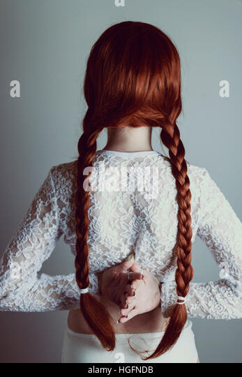 Young redhead woman with two long braids back to the camera - Stock Image