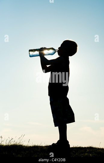 Boy drinking mineral water from plastic water bottle. Silhouette - Stock Image