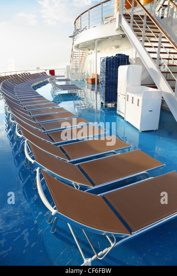 row of chaise longues on deck of cruise ship. golden morning sun shining. - Stock Image