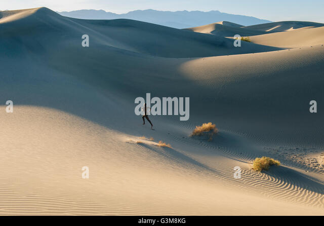 Nude woman in desert running up dune - Stock Image