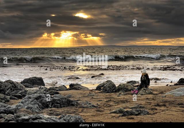 Ireland, Munster, County Waterford, Tramore, Girl (4-5) sitting on rock at beach - Stock-Bilder