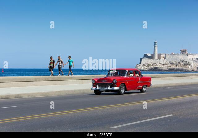Cuba, Ciudad de la Habana province, La Havana, american car on the Malecon and the lighthouse of the Castillo de - Stock Image