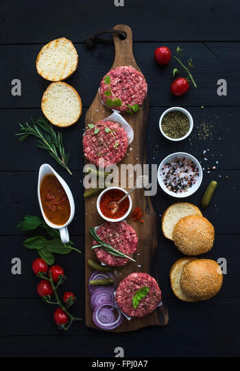 Ingredients for cooking burgers. Raw ground beef meat cutlets on wooden chopping board, red onion, cherry tomatoes, - Stock Image
