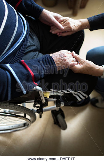 Senior woman holding hands of her ill husband in a nursing home - Stock-Bilder