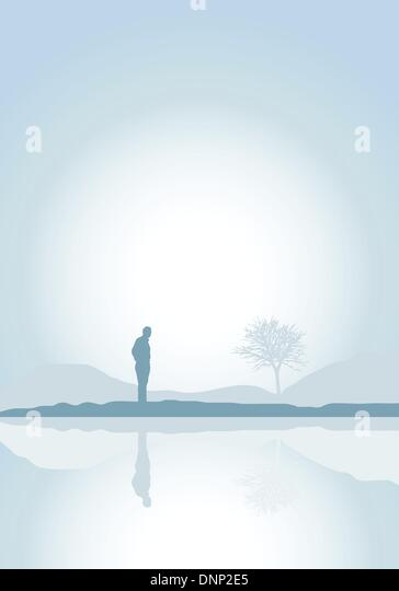 Silhouette of a solitary man by a lake - Stock Image