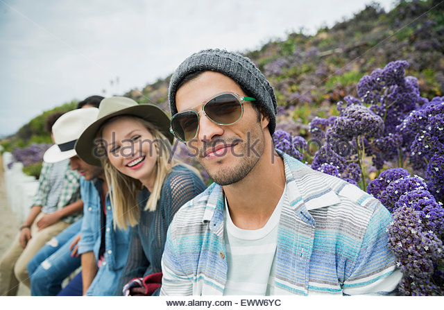 Portrait smiling friends sitting in a row - Stock Image