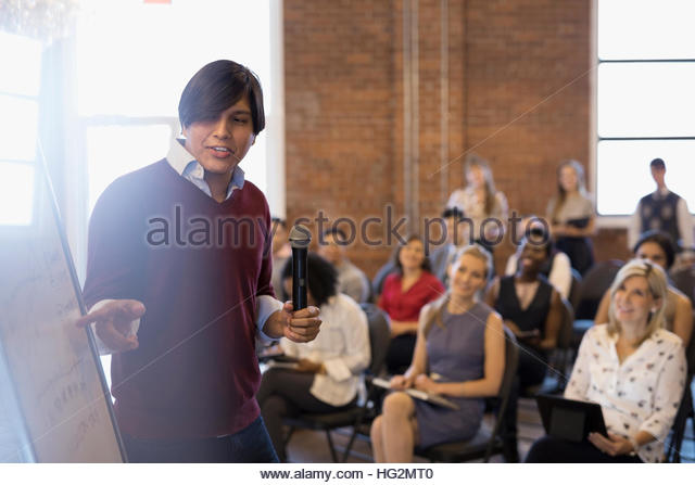 Businessman leading conference meeting at whiteboard in conference room - Stock Image