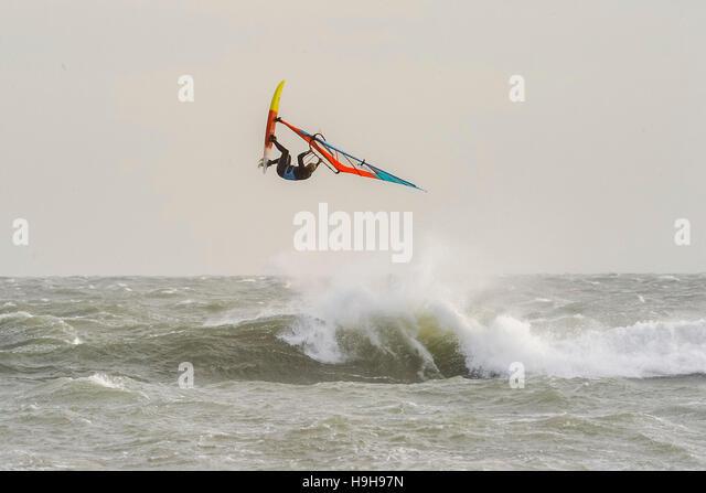 Weymouth, Dorset, UK.  24th November 2016.  UK Weather.  A windsurfers taking advantage of  the strong winds and - Stock Image