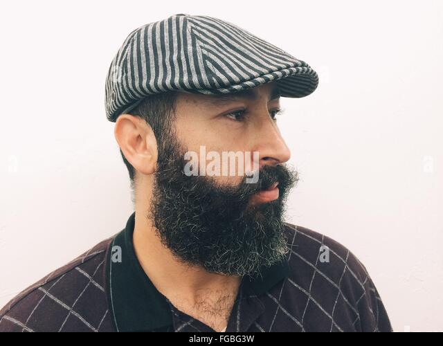 Side View Of Mature Man With Beard Wearing Hat Against White Background - Stock-Bilder
