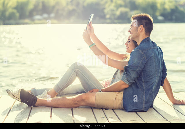 Couple in love sitting on the pier, selfie - Stock-Bilder