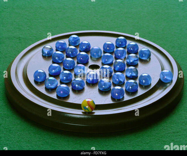 Solitaire marbles board game on green baize - Stock Image