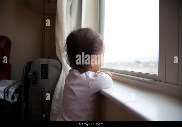 Child looking out apartment window stock photos child for 2 year old falls out of window