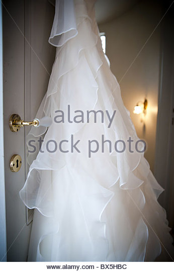 Bridal wedding dress hanging from a door - Stock Image