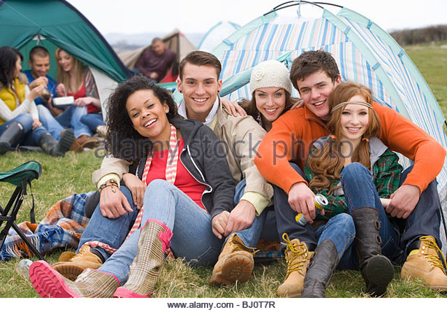 Happy couples camping in tent and attending outdoor festival - Stock Image