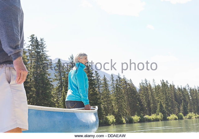 Couple carrying canoe to the river - Stock Image
