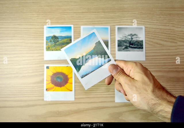 Person's hand picking a photo among six options - Stock Image