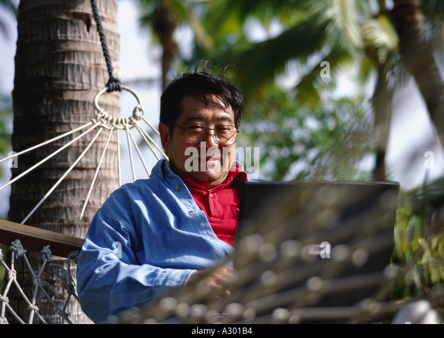 a chinese aged man sitting in a hammock with a laptop on his knees and typing - Stock-Bilder